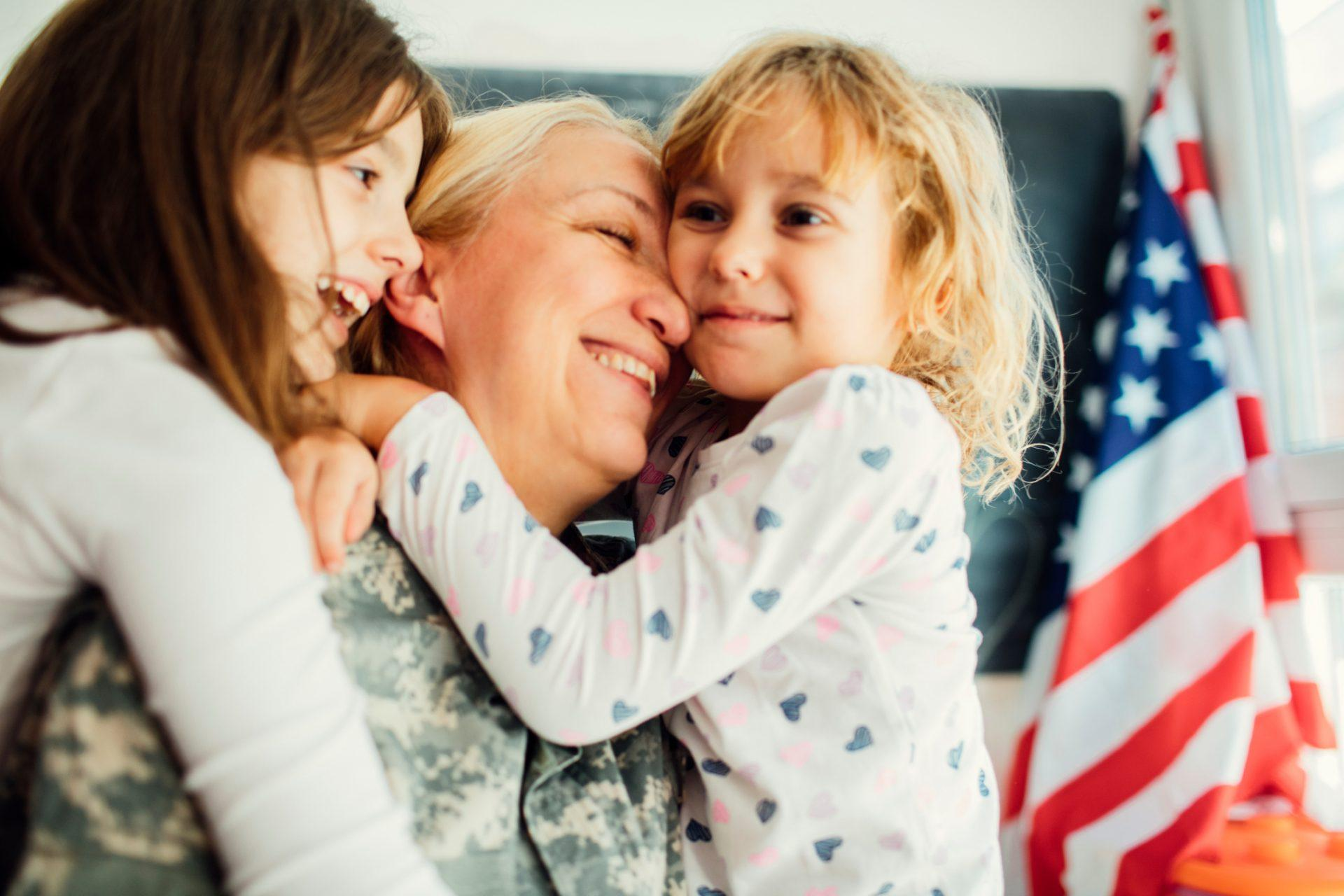 Military mom hugging with her two children, little girls. They are hugging each other, smiling with tears of joy. Having some happy time together. Mother just return from some of army missions. Shot with Canon EOS 5Ds 50mp